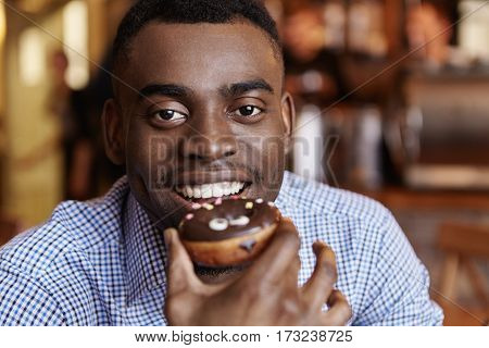 Portrait Of Cheerful Young African Male Wearing Formal Checkered Shirt Holding Glazed Doughnut, Read