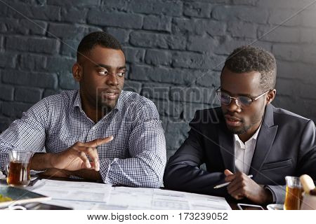 Two African-american Businessmen Discussing Business Plans At Office: Male In Suit And Glasses Holdi