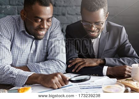 Two Happy Dark-skinned Businessmen Reading Documents With Magnifying Glass, Analyzing Financial Agre