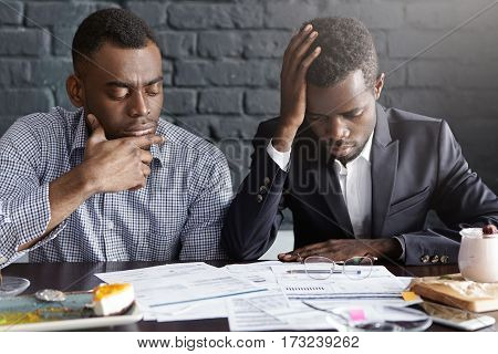 People, Business And Failure. Two Tired And Depressed African-american Businessmen Doing Paperwork,