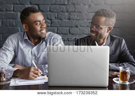Two Successful And Experienced African-american Executives Smiling Happily, Talking To Each Other Du