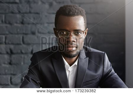 Close-up Shot Of Handsome Young Dark-skinned Entrepreneur In Spectacles And Formal Wear Having Serio