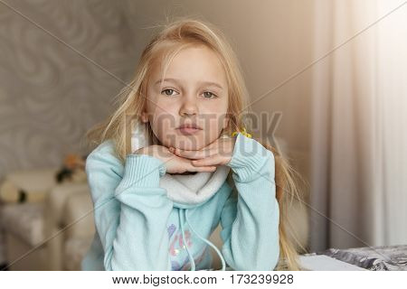 Sad Or Bored Little Blonde Girl Of Caucasian Appearance Resting Face On Her Clasped Hands, Forced To