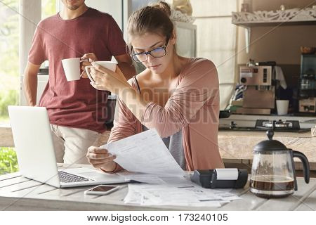 Young Caucasian Family Calculating Bills, Reviewing Finances And Planning Family Budget Together In