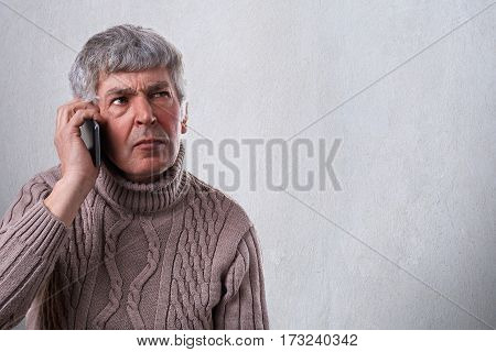 A horizontal portrait of serious worried upset mature man talkiing on cellphone. An old employee deciding some problems over telephone. Human face expression emotion reactions life perception