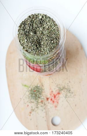 A stack of jars with spices on a wooden background. Oriental spices and seasonings.