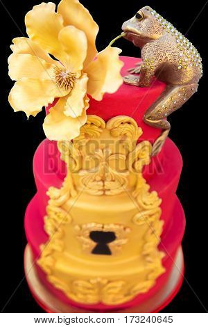 golden frog with a flower in the mouth is decorated with high red cake at a wedding party