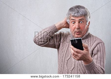 Portrait of surprised senior man looking with wide open eyes into his smartphone being shocked by what he sees on his cell phone. Human face expressions. Surprise astonishment wonder