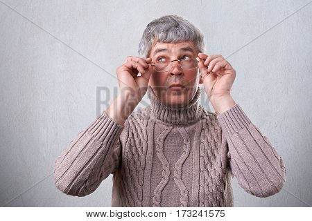 A mysterious senior man with gray hair wearing eyeglasses looking aside. Clever adult touching his glasses thinking about something dressed in sweater isolated over white background
