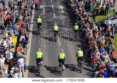 Zurich, Switzerland - 13 April, 2015: people and police bicyclists on Uraniastrasse street before the beginning of the Sechselauten parade. The Sechselauten is a traditional spring holiday in the city of Zurich.