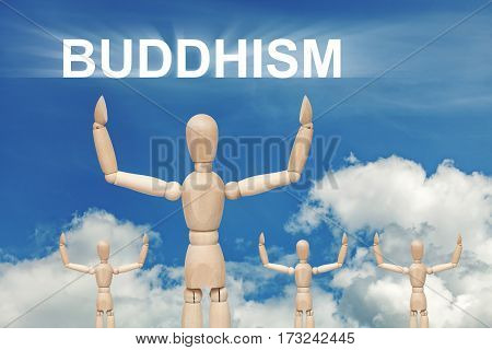 Wooden dummy puppet on sky background with text BUDDHISM. Abstract conceptual image