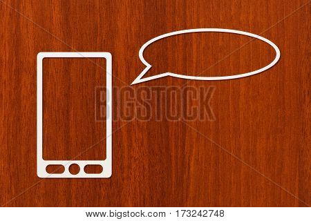 Paper tablet or smartphone with speech bubble or balloon copyspace dark wooden background. Abstract conceptual image