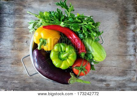 Fresh vegetables tomato zucchini eggplant sweet pepper hot pepper metal colander wooden table .A healthy way of life. Dark background copy space close-up. The view from the top