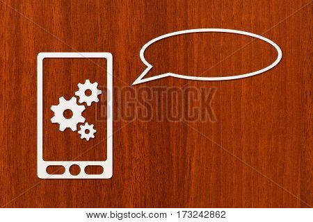Paper tablet or smartphone with cogwheels and speech bubble copyspace dark wooden background. Abstract conceptual image