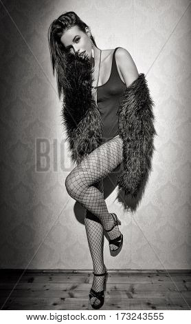 Fashionable sexy woman posing at vintage wal at night black and white