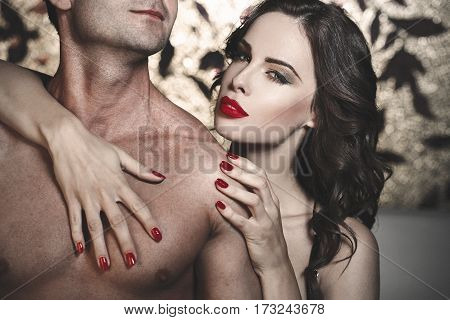 Sexy woman with red lips embracing young lover closeup