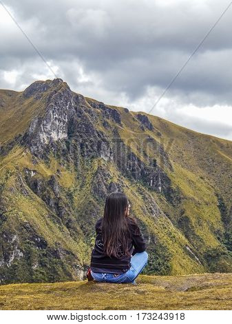 QUITO, ECUADOR, OCTOBER - 2015 - Back view of adult young woman with black straight hair contemplating the landscape of andes range in Quito Ecuador