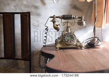 Old-fashioned retro rotary telephone on wood table