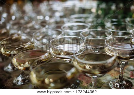 A lot of wine glasses with champagne on the table at the ceremony. Glasses with alcoholic drinks.
