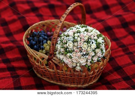 boquet and different fruits in wicker basket on plaid