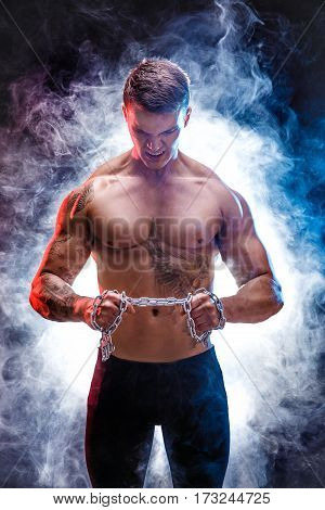 Portrait of muscular tattooed sportsman with metal chain. Background with smoke