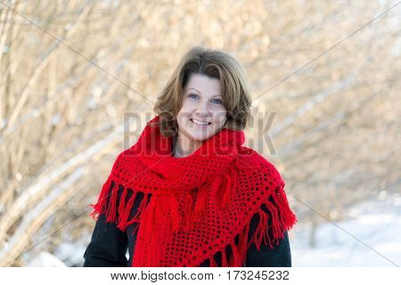 Beautiful woman with red knitted shawl on the shoulders of the outside