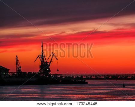 Novgorod. Volga river. Silhouettes of cranes against a red sunset. River Bridge.
