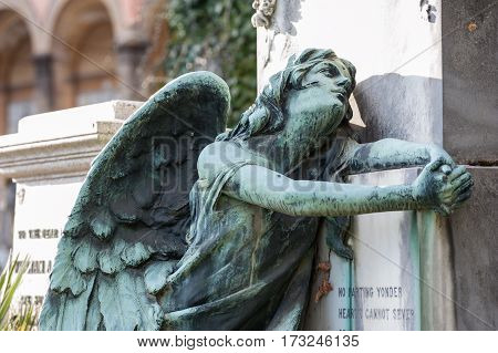 The afflicted angel kneeling on the tomb turns his gaze to the sky praying to God