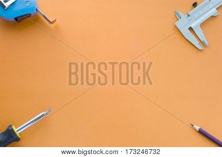 procurement of construction poster tape measure pencil screwdriver lying on the background of the orange on the table