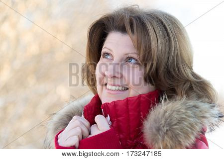 A woman in a jacket with a fur collar dreamily looking up