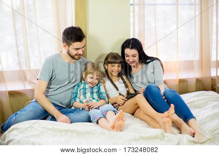 Modern technology in home. Young family, the use of tablets, lying in bed at home