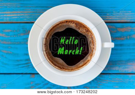 Hello March - text with a cup of morning coffee at blue wooden background. Top view. Springtime.