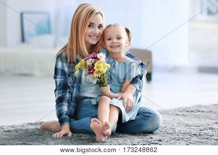 Beautiful young woman and her daughter sitting on carpet at home. Mother's day concept