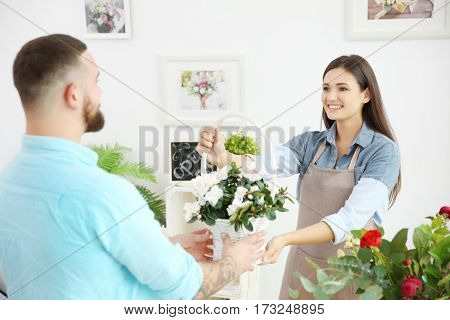Pretty young florist giving basket with flowers to customer, close up view