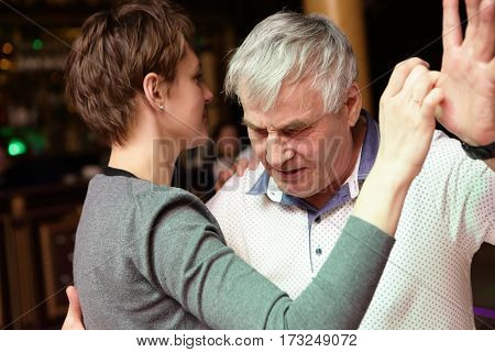 Senior man dancing with his daughter in club