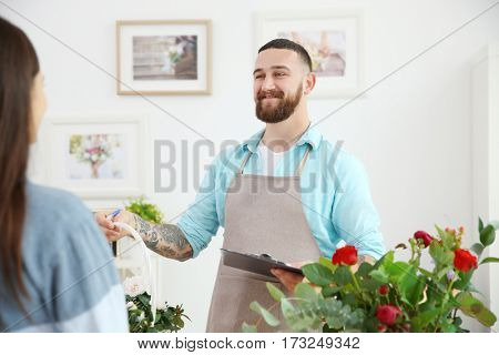 Handsome florist giving basket with flowers to customer