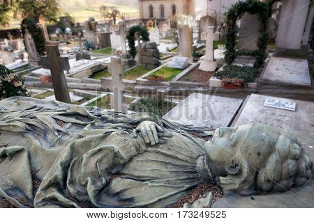 The dead old woman body statue with her arms crossed lying over the gravestone rest in peace at the cemetery