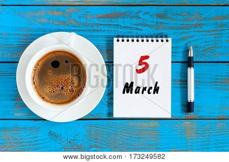 March 5th. Day 5 of month, calendar written on morning coffee cup at blue wooden background. Spring time, Top view.