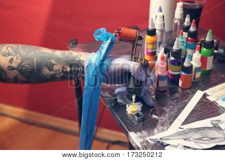 Hand of professional artist with tattoo machine and plastic cups with colorful inks, close up view