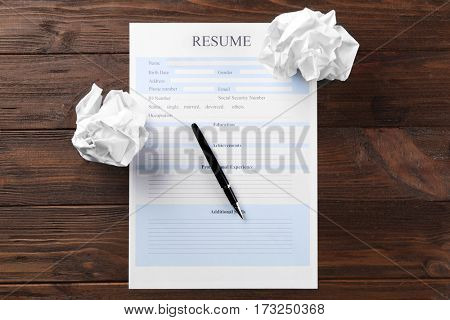 Blank resume form and crumpled paper on wooden table