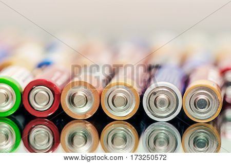 Closeup of pile of used alkaline batteries. Close up colorful rows of selection of AA batteries energy abstract background of colorful batteries. Alkaline battery aa size. Several batteries are next to each other. Many aa batteries.