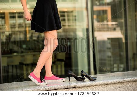 Young woman  on street in sneakers and high heels shoes are next to her