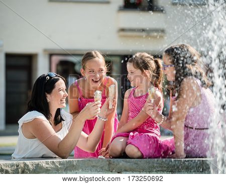 Smiling mother offering ice-cream to kids. Family sitting near the fountain.