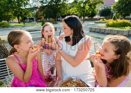 Happy family sharing pizza while sitting on park bench