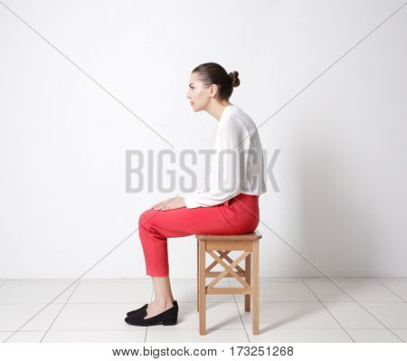Incorrect posture concept. Young woman sitting on stool against white wall background
