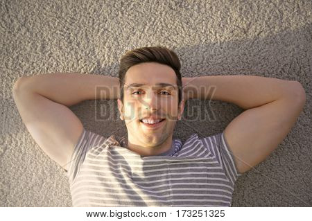 Happy young man lying on soft carpet in light room