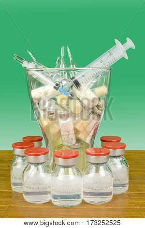 Medicines in a vase on a green background. For the treatment and injection