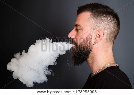 a beared man smoking the electronic cigarette