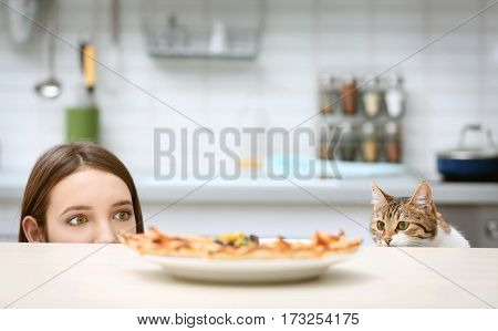 Young woman and cute cat looking at plate with tasty pizza in kitchen