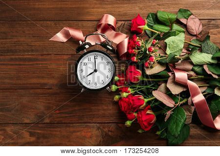 Beautiful red roses and alarm clock on wooden background